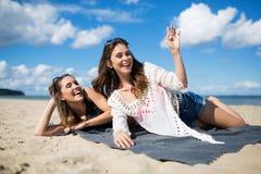 2 молодой женщины лежа на пляже имея потеху Стоковая Фотография RF