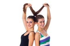 2 молодой женщины держа их волосы Стоковая Фотография