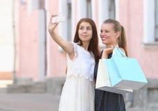 2 молодой женщины держа хозяйственные сумки и принимая автопортрет Стоковые Фото