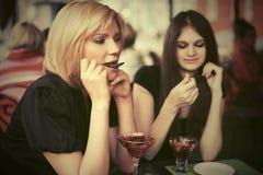 2 молодой женщины есть десерт на кафе тротуара Стоковые Фотографии RF