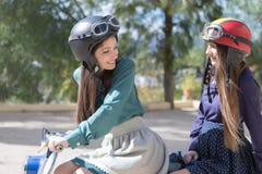 2 молодой женщины ехать винтажное moto Стоковые Изображения