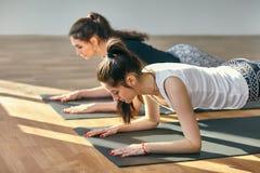 2 молодой женщины делая представление планки asana йоги низкое Стоковые Фотографии RF
