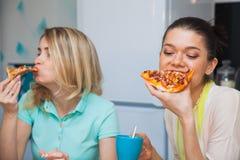 2 молодой женщины едят пиццу Еда вкуса девушек итальянская традиционная Стоковая Фотография RF