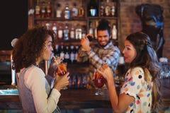 2 молодой женщины имея пить коктеиля на счетчике Стоковые Фотографии RF
