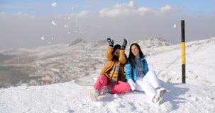 2 молодой женщины имея потеху в снеге зимы Стоковые Изображения