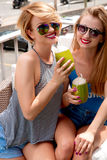 2 молодой женщины имея потеху и выпивая коктеиль в летнем дне Стоковые Изображения