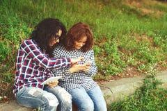 2 молодой женщины используя планшет outdoors Стоковая Фотография