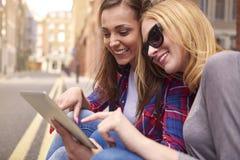 2 молодой женщины используя таблетку Стоковые Фотографии RF