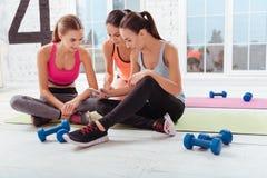 3 молодой женщины используя smartphone в спортзале Стоковая Фотография