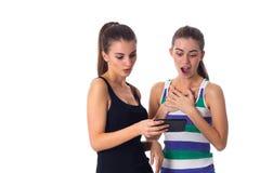 2 молодой женщины используя smartphone Стоковое Фото