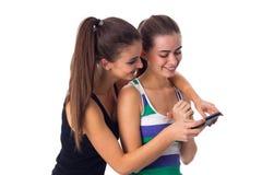 2 молодой женщины используя smartphone Стоковые Фотографии RF
