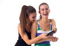 2 молодой женщины используя smartphone Стоковая Фотография