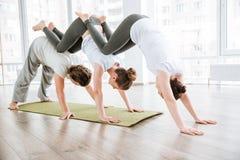 2 молодой женщины и йога acro человека практикуя Стоковая Фотография RF