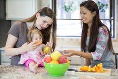 2 молодой женщины и маленькая девочка в кухне Стоковые Фото