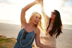 2 молодой женщины наслаждаясь каникулами пляжа Стоковая Фотография