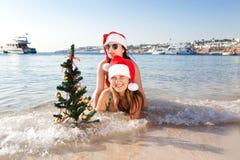 2 молодой женщины на пляже празднуя праздники Нового Года Стоковая Фотография