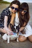 2 молодой женщины на пляже принимая фото с французским бульдогом Стоковая Фотография