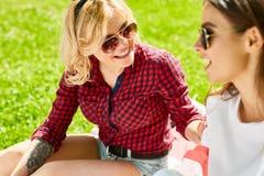 2 молодой женщины ослабляя на лужайке в парке Стоковое Изображение RF