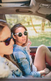 2 молодой женщины отдыхая сидеть внутри автомобиля Стоковое Фото