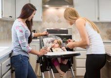 2 молодой женщины подавая маленькая девочка в высоком стульчике Стоковые Фотографии RF