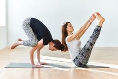 2 молодой женщины практикуя представления и asanas йоги Стоковые Фотографии RF