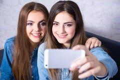 2 молодой женщины принимая фото selfie с умным телефоном Стоковые Фото
