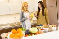 2 молодой женщины провозглашать с белым вином в современной кухне Стоковое фото RF