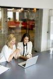 2 молодой женщины работая на подоле покрывают в офисе Стоковая Фотография RF