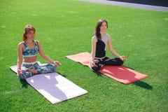 2 молодой женщины размышляют сидеть на зеленой лужайке Стоковые Фотографии RF