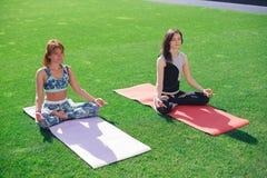 2 молодой женщины размышляют сидеть на зеленой лужайке Стоковые Фото