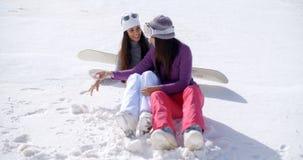 2 молодой женщины сидя беседовать в снеге Стоковые Изображения