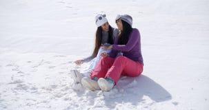 2 молодой женщины сидя беседовать в снеге Стоковая Фотография