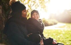 2 молодой женщины сидя в парке и усмехаться Стоковое Изображение