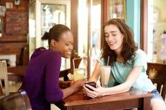 2 молодой женщины сидя на кафе с мобильным телефоном Стоковая Фотография