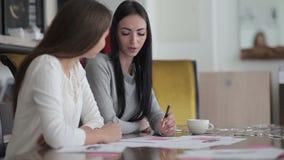 2 молодой женщины сидя на таблице в офисе акции видеоматериалы