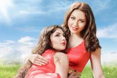 2 молодой женщины сидя на траве Стоковые Изображения RF