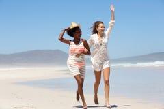 2 молодой женщины смеясь над и играя на пляже Стоковые Изображения RF