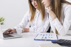2 молодой женщины смотря компьтер-книжку Стоковое Фото