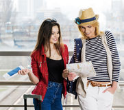 2 молодой женщины стоят с чемоданом на железнодорожном вокзале или авиапорте Посмотрите карточку и пасспорт Стоковое фото RF