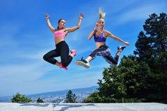 2 молодой женщины счастья скача над голубым небом Стоковая Фотография