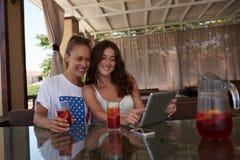 2 молодой женщины с красивыми улыбками наблюдая совместно смешное видео на цифровой таблетке пока сидящ в уютном ресторане, Стоковые Фото