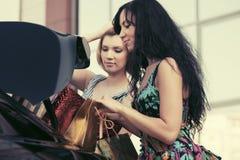 2 молодой женщины с хозяйственными сумками на автостоянке автомобиля Стоковая Фотография
