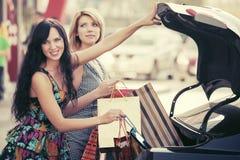 2 молодой женщины с хозяйственными сумками на автостоянке автомобиля Стоковые Изображения RF