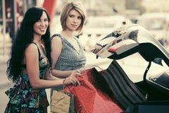 2 молодой женщины с хозяйственными сумками на автостоянке автомобиля Стоковые Фото