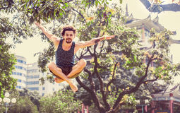 Молодой жизнерадостный человек скача в парк Стоковое фото RF