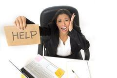 Молодой занятый отчаянный латинский знак помощи удерживания коммерсантки сидя на столе офиса в стрессе потревожился Стоковое Фото