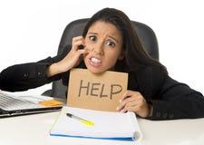 Молодой занятый отчаянный латинский знак помощи удерживания коммерсантки сидя на столе офиса в стрессе потревожился Стоковое фото RF