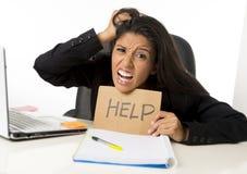 Молодой занятый отчаянный латинский знак помощи удерживания коммерсантки сидя на столе офиса в стрессе потревожился Стоковая Фотография RF