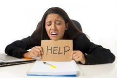 Молодой занятый отчаянный латинский знак помощи удерживания коммерсантки сидя на столе офиса в стрессе потревожился Стоковое Изображение RF
