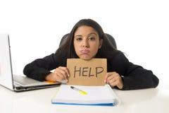 Молодой занятый отчаянный латинский знак помощи удерживания коммерсантки сидя на столе офиса в стрессе потревожился Стоковые Фотографии RF